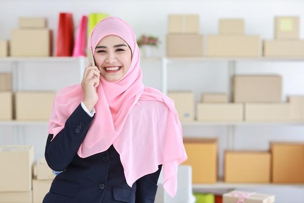 青いスーツとピンクのシャフトの宗教的なアジアのイスラム教徒の女性が立って、自信を持って携帯電話を使用し、ビジネスパッケージsmeボックス配信の背景。