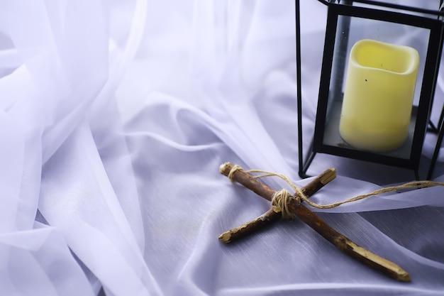 종교 개념입니다. 흰색 바탕에 수제 나무 십자가입니다. 촛불과 와인 글라스 램프입니다.