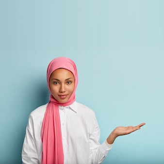 Religious confident muslim woman seller raises palm over blank space, holds invisible object, wears pink silk scarf on head, promots item, stands against blue wall, dressed in white shirt
