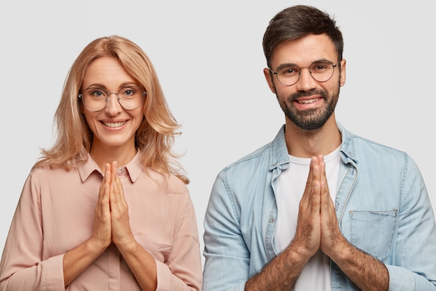 Religious family couple with happy expressions, make praying gesture, believe in well being
