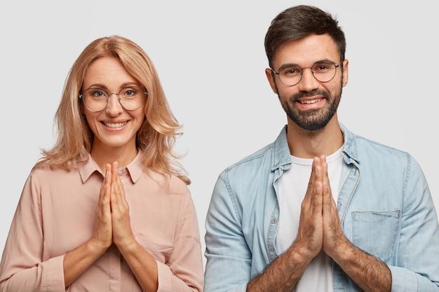 Coppia di famiglia religiosa con espressioni felici, fa un gesto di preghiera, crede nel benessere