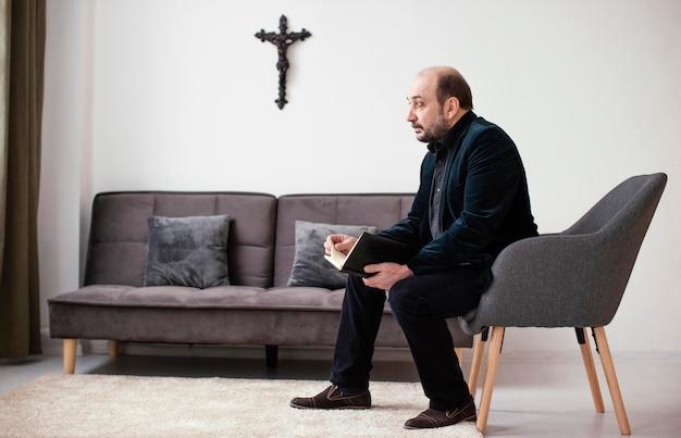 Религиозный мужчина держит священную книгу в помещении