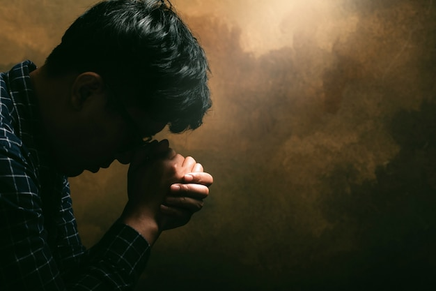 Religious man praying to god resting his chin on his hands.his hands are praying for god's blessings.