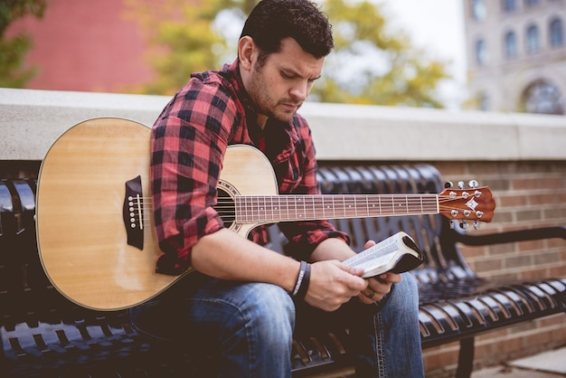 A religious man with a guitar reading the bible outdoors