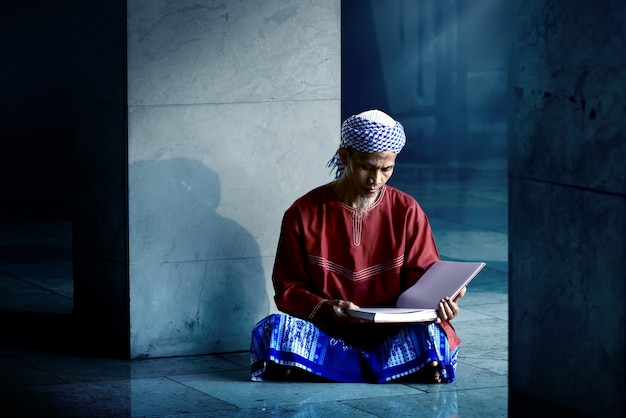 Religious muslim man reading holy koran
