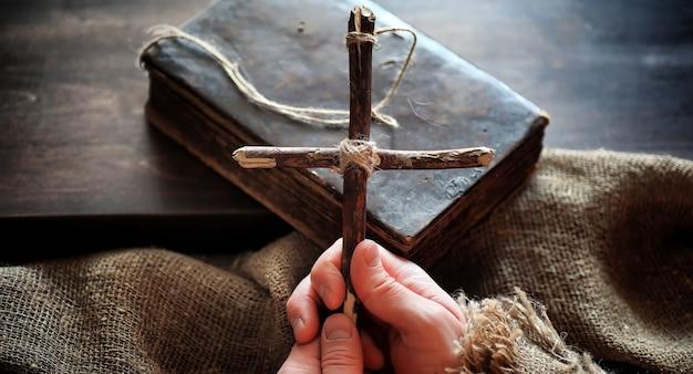 木製のテーブルに置かれた宗教的な古書。聖書の隣にロープと黄麻布で結ばれた宗教的な十字架。崇拝、罪、そして祈り。