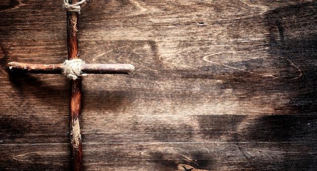 木製のテーブルの上の宗教的な古い本。聖書の隣にロープと黄麻布で結ばれた宗教的な十字架。礼拝、罪、そして祈り。