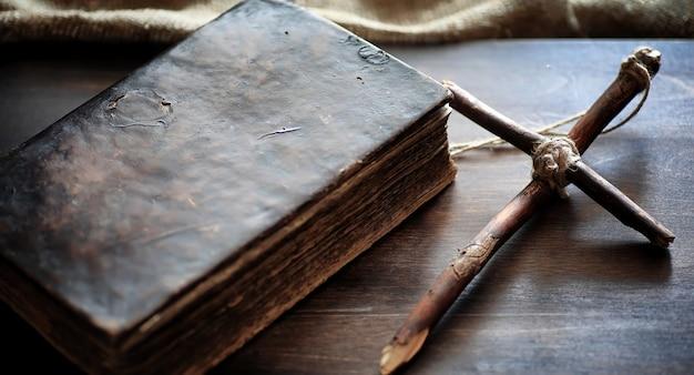 나무 테이블에 종교적인 오래 된 책입니다. 성경 옆에 밧줄과 삼베로 묶인 종교 십자가. 예배, 죄와 기도.