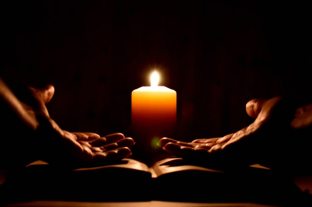 Religious prayer with a candle in complete darkness.