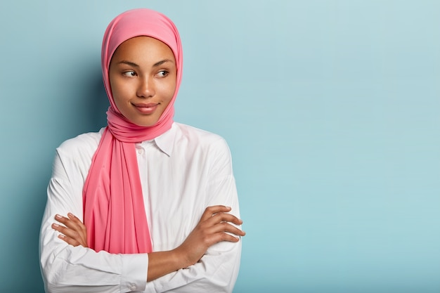 Religious satisfied female model has arms folded, looks aside, has pleased expression, wears pink scarf on head, white shirt, being deep in thoughts, stands over blue wall, copy space for text