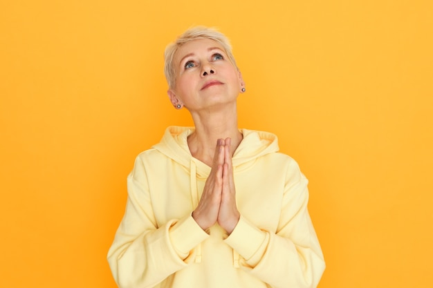 Religious unhappy woman pensioner with hopeful eyes posing isolated holding hands pressed together looking up while praying, pleading, asking god for help and guidance, being depressed in hard times