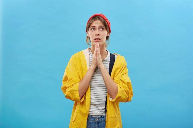 Moglie religiosa in abbigliamento casual tiene insieme i palmi delle mani pregando per il benessere del marito che è venuto a caccia in un luogo pericoloso. giovane bella casalinga che chiede tutto il bene della sua vita