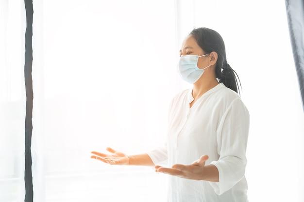 保護マスクを着用し、自宅で助けを求めて神に祈る宗教的な女性。医療用フェイスマスクの女の子のキリスト教の祈り。コロナウイルスcovid-19