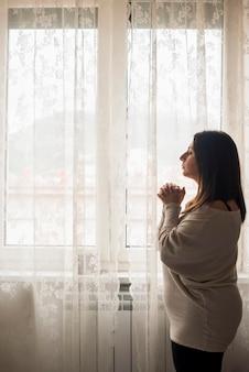 家で助けを祈る宗教的な女性