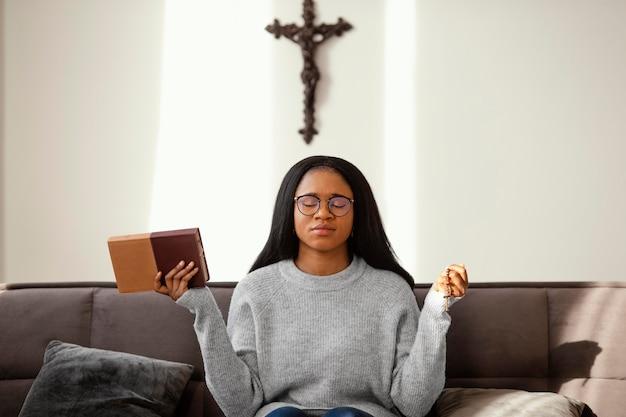 집에서 묵주 구슬로기도하는 종교적인 여자