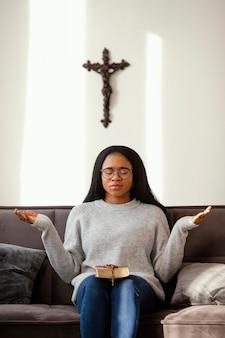 Религиозная женщина молится с четками