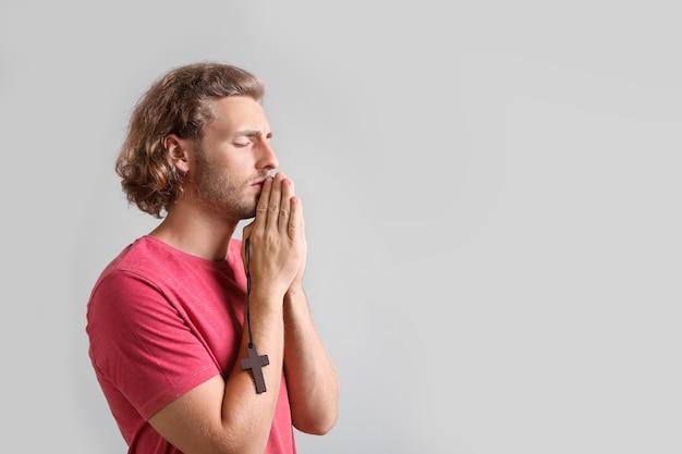 灰色で祈る宗教的な若い男