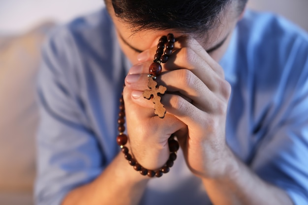 Religious young man with rosary beads praying at home, closeup