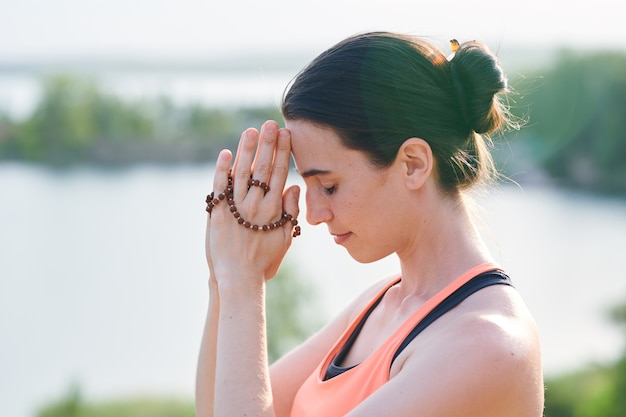 Religious young woman with hair bun joining hands together with beads while praying outdoors