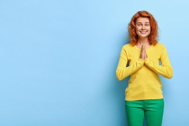 Rivive la calma sorridente giovane donna con i capelli rossi ondulati, preme i palmi insieme