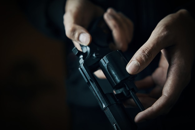 재장전 총 근접 촬영 남자 손은 리볼버 배럴에서 총알을 확인합니다. 사람이 발사를 준비합니다...