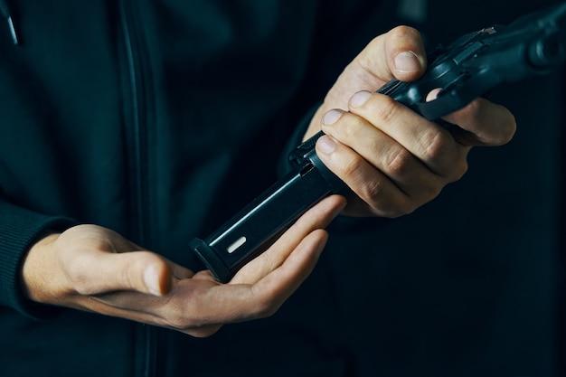 권총 근접 촬영을 다시 장전하는 남자는 어두운 배경에서 손에 든 총기에 카트리지 드럼을 삽입합니다...