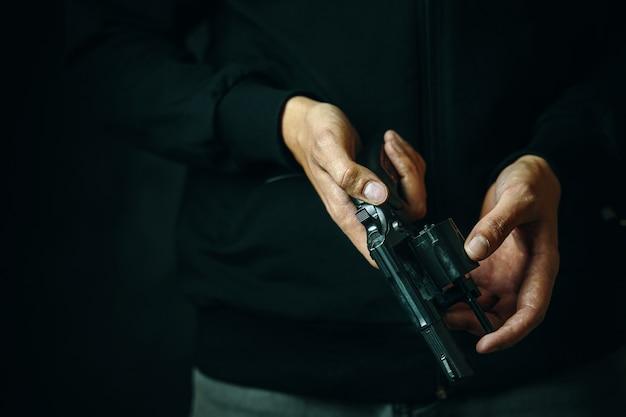 リボルバーのクローズアップメンズハンドをリロードすると、ジーンズと黒のパーカーの銃身の男の弾丸をチェックします...