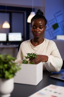 Relocated african american businesswoman putting objects in cardboard box