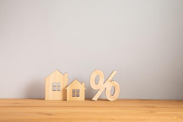 재배치 및 집 사냥 개념. 기호 %와 목조 주택 모델