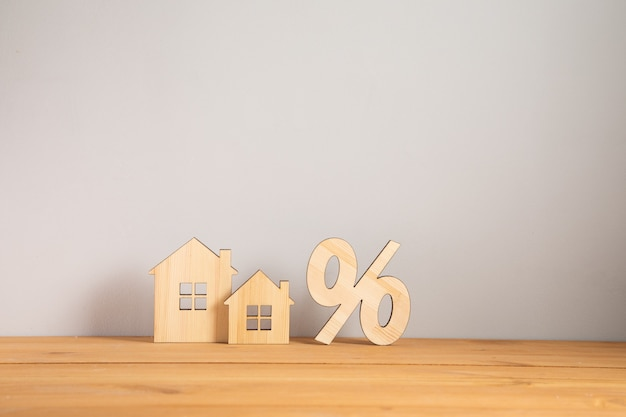 Relocation and house hunting concept. model of wooden house with sign percent