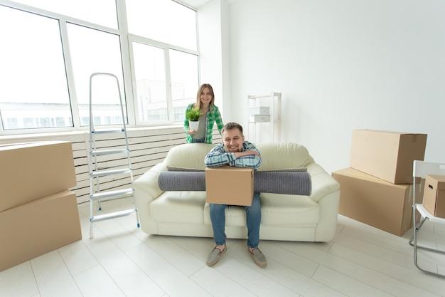 Переезд, недвижимость и концепция переезда - молодая веселая пара переезжает в свой новый дом