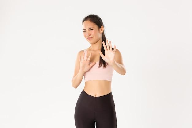 거부감에 악수하고 찡그린 표정을 짓고 혐오스러운 일에 움츠러 드는 활동복을 입은 아시아 여성 운동 선수가 거부하고 불쾌한 제안을 거부합니다.