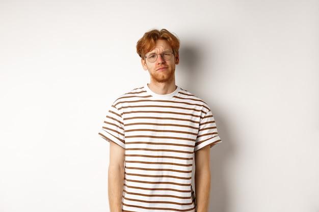 カメラを見つめ、疲れているか不快に見え、白い背景の上に立っている、気が進まない、面白くない赤毛の若い男。