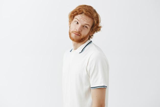 白い壁に向かってポーズをとる気が進まないひげを生やした赤毛の男