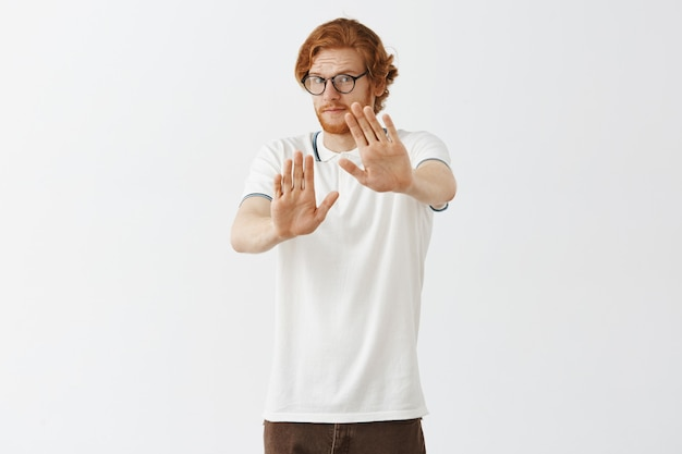 Reluctant bearded redhead guy posing against the white wall with glasses