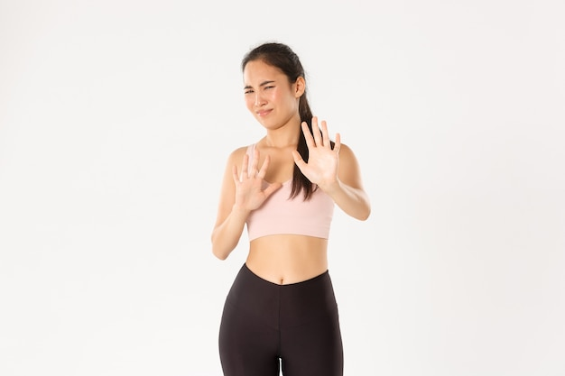 Reluctant and displeased asian female athlete in activewear shaking hands in rejection, grimacing and cringe over something disgusting, refuse offer.