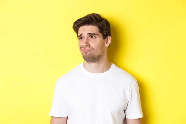 Reluctant guy in white t-shirt looking left, grimacing skeptical and displeased, standing over yellow background
