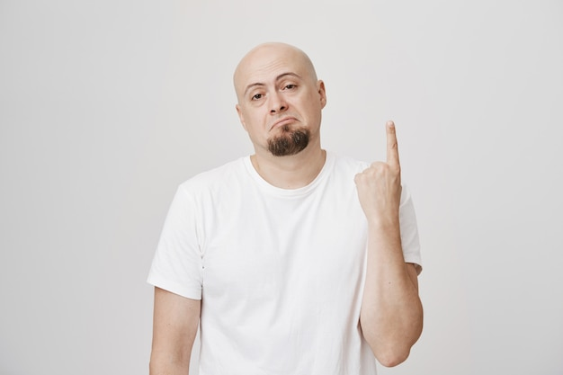 Reluctant middle-aged man showing forefinger, pointing up