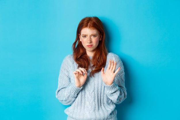 멀리 떨어져 있고, 거절 제스처로 악수하고, 제안을 거절하고, 파란색 배경 위에 서서 불쾌한 찡그린 표정을 짓는 것을 꺼리는 빨간 머리 소녀.