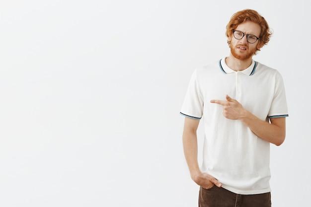 Ragazzo rosso barbuto riluttante e triste in posa contro il muro bianco con gli occhiali