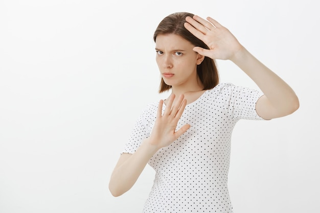 Reluctant serious woman staying away from something, raising hands in stop gesture, defending herself