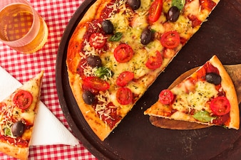 Remain slices of pizza on wooden tray with drinks in the glass