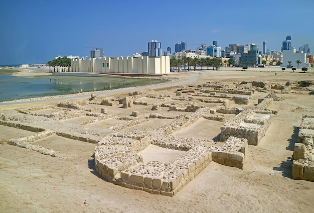 Remains of bahrain fort structure with manama modern cityscape in the backdrop manama bahrain