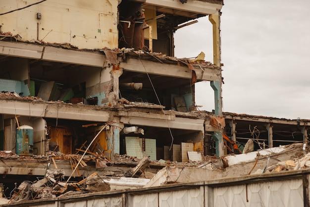 Остатки разрушенного производственного здания с внутренними коммуникациями. снос здания на территории завода. фон с полуразрушенным зданием и фрагментами кирпича и строительного мусора