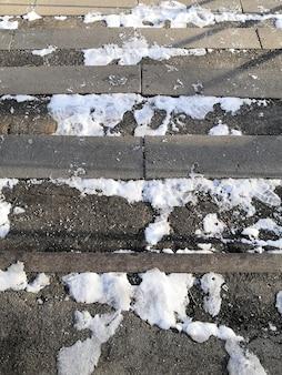 冬の晴れた日の古いコンクリートの階段の雪と氷の残骸