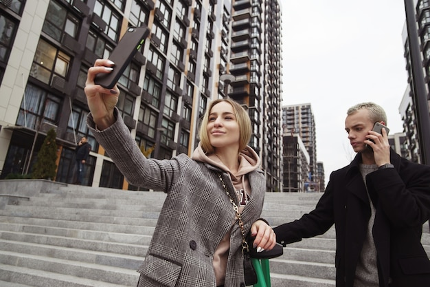 この瞬間を忘れないでください!スマートフォンを持って彼氏と一緒に自分撮りをしている若い女性。秋の街を歩いている若いカップル。背景のアパートのブロック。電話で話している男。