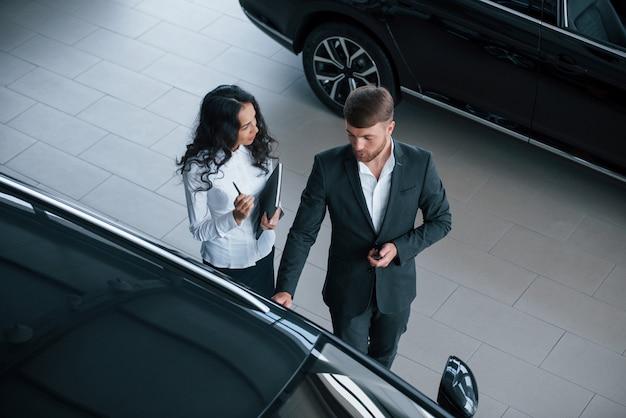 회의에서 할 말을 기억하십시오. 여성 고객과 자동차 살롱에서 현대적인 세련된 수염 사업가