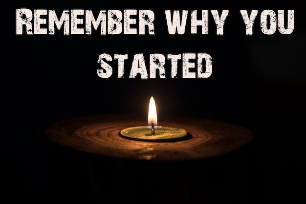 Remember why you started - white candle with dark background - in a wooden candlestick.