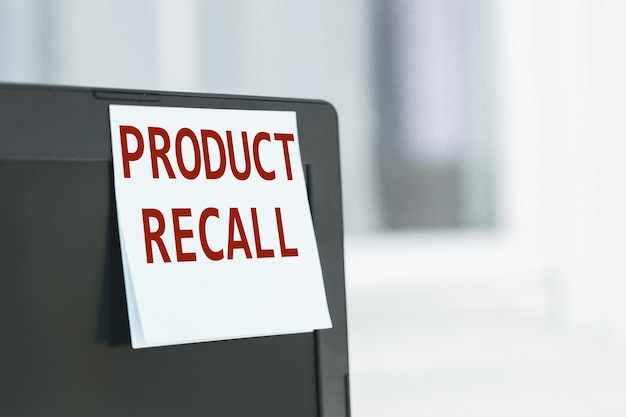 オフィスのコンピューターモニターに貼られた白い紙のステッカーに、「製品のリコール」というテキストが記載されたリマインダー。ビジネスコンセプト