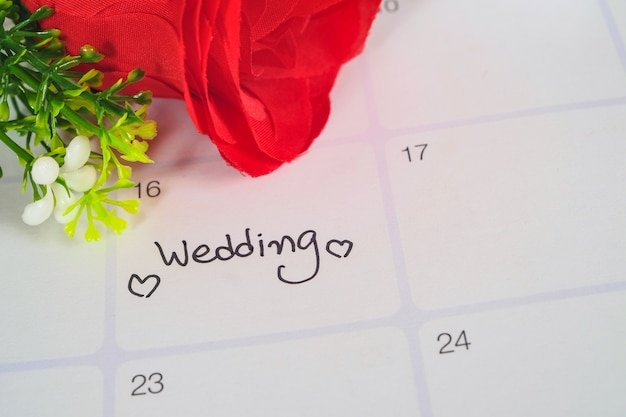 Reminder wedding day in calendar planning with red rose.